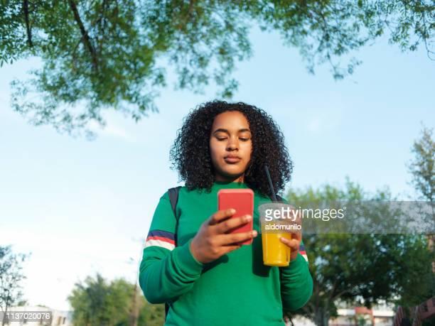 飲み物とテキストメッセージを保持している女子大生