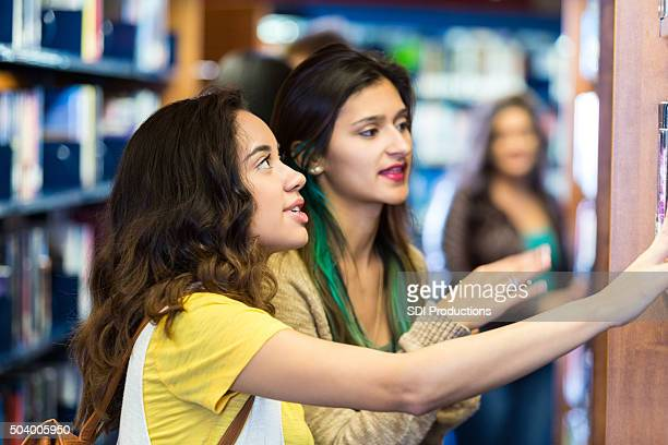 College girls searching for books in library or book store