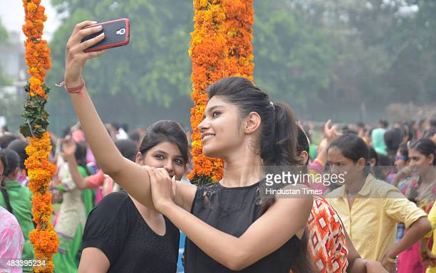 College girls taking a selfie during the celebrations of Teej festival arranged at Khalsa College for Women on August 8 2015 in Amritsar India The...