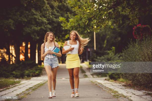 college girls walking to classes together - mini skirt stock pictures, royalty-free photos & images