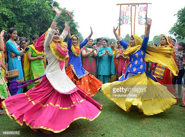 College girls wear traditional Punjabi dress as they perform Giddha dance during the celebrations of Teej festival arranged at Khalsa College for...