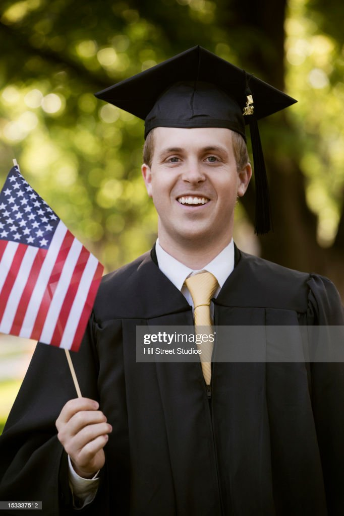 College Graduate In Cap And Gown Holding American Flag Stock Photo ...