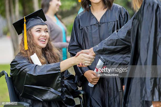 College graduate in wheelchair shakes hands with classmate