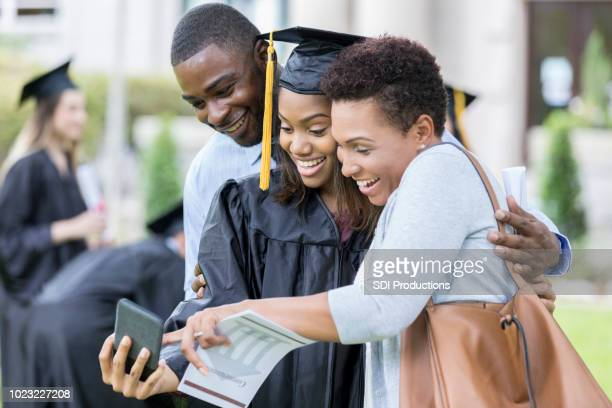 College graduate taking selfie with parents
