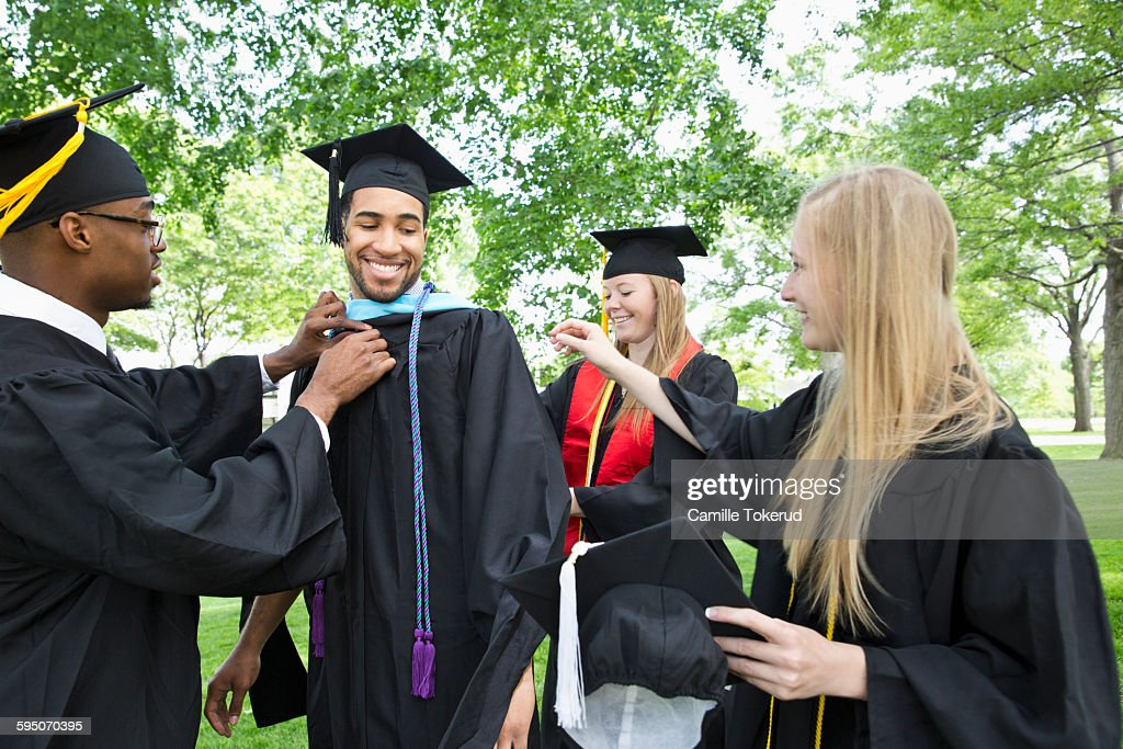 College Graduates Helping Organize Cap And Gown Stock Photo | Getty ...