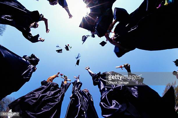 college graduates throwing caps - graduation clothing stock pictures, royalty-free photos & images