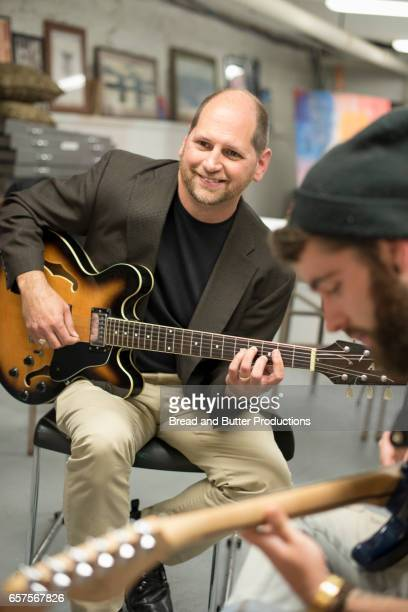 College guitar teacher leading music class with students