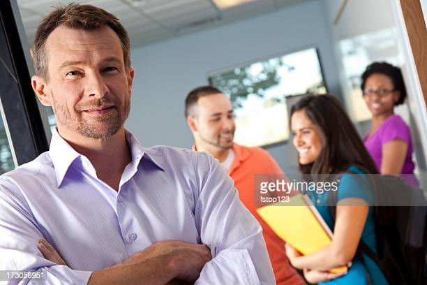 College instructor at door, young adult students in classroom. Professor.