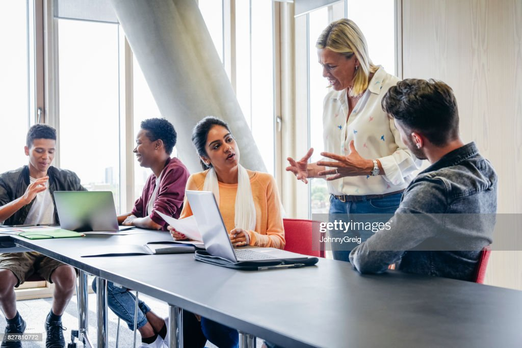 College lecturer explaining to small group of students in classroom : Stock Photo