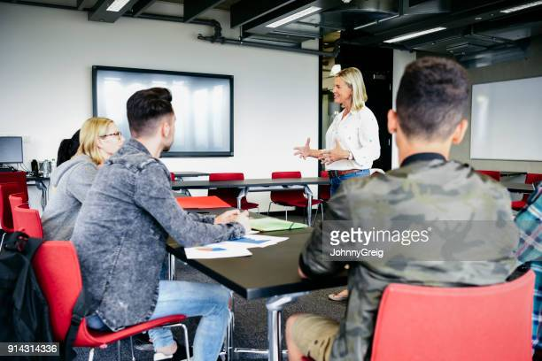 college lecturer talking to young students in modern classroom - college professor stock photos and pictures