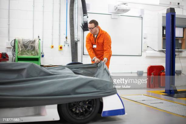 College mechanic student removing racing car cover in repair garage