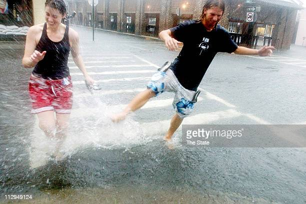 College of Charleston students Sally Berton left of Nebraska and Greg Rockwell of Fort Mill splash each other while walking along Market Street as...