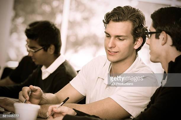 Collège universitaire des étudiants masculins en prenant des notes dans une salle de classe