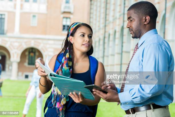 College professor talks with student on campus