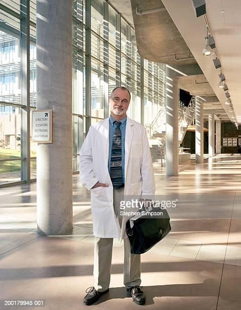 college professor wearing lab coat standing in science building - dokterstas stockfoto's en -beelden