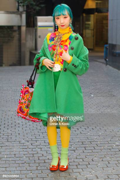 College student and performer Miochin with dyed blue hair bright green wool coat yellow turtleneck sweater floral print shirt rainbow scarf large...