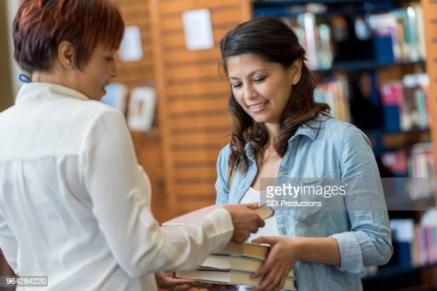 estudiante universitario comprueba hacia fuera los libros de la biblioteca del campus - devolución del saque fotografías e imágenes de stock