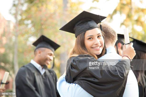 college student excitedly hugs father after graduation ceremony. - ceremony stock pictures, royalty-free photos & images