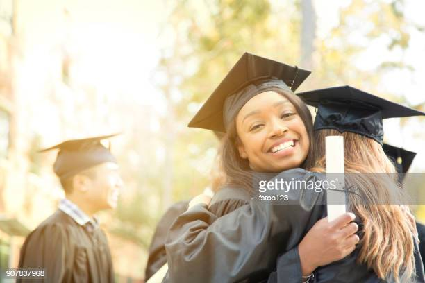 College student friends excitedly hug after graduation ceremony.