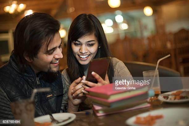 college student friends learning and teaching together in a restaurant. - man eating woman out stock photos and pictures