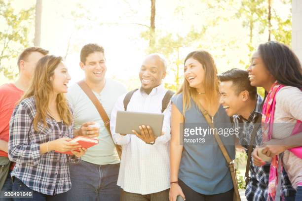 College student friends share digital tablet on university campus.