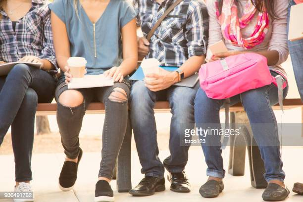 College student friends sitting on university campus bench.