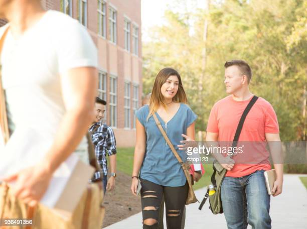 College student friends walking to class on university campus.