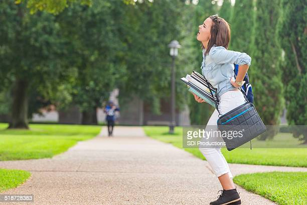 college student holding heavy books while walking on campus - shoulder bag stock pictures, royalty-free photos & images