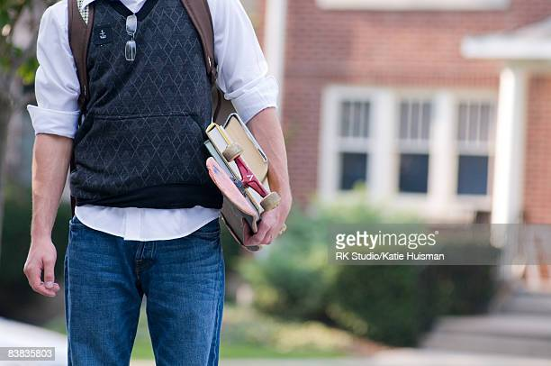 College Student Holding Textbooks and Skateboard