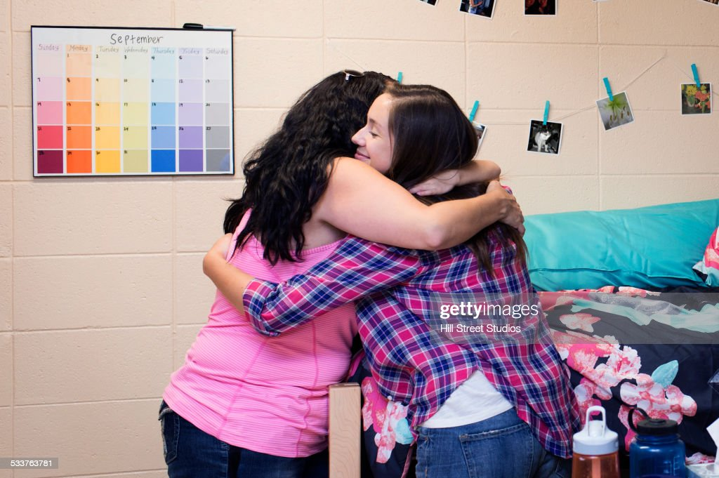 College student hugging mother in dormitory room : Stock Photo