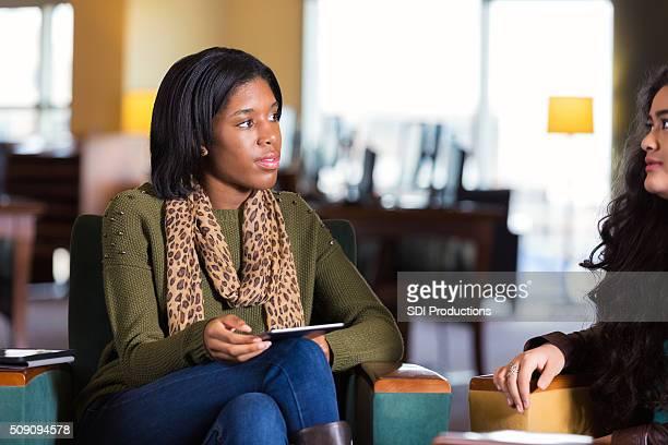 Estudante universitário tutoria jovem rapariga, reunião na biblioteca