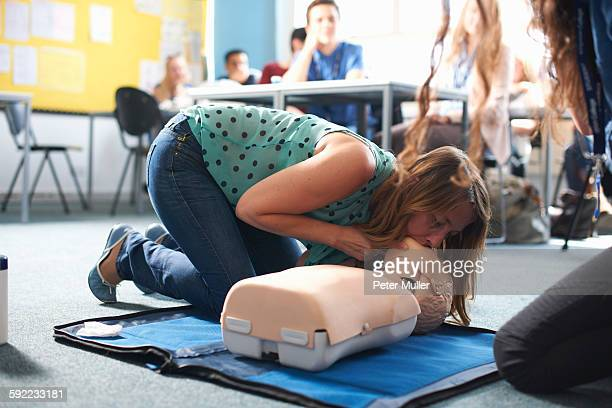 College student performing CPR on mannequin in class