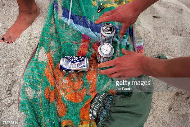 A college student reaches for his beer as he relaxes March 14 2007 on South Beach in Miami Beach Florida Students from Universities around the...