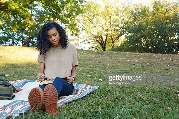 College Student reading in a city park