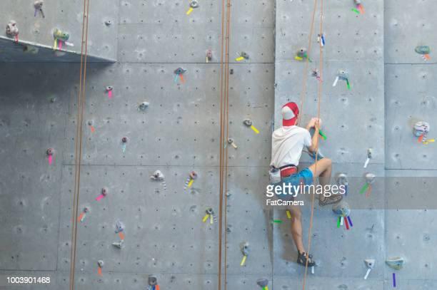 大学生の屋内上昇の壁をスケーリング - クライミングウォール ストックフォトと画像