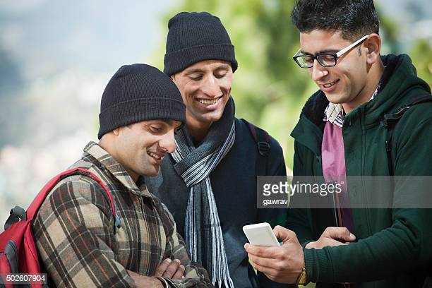 College student showing new features of smartphone to his friends.