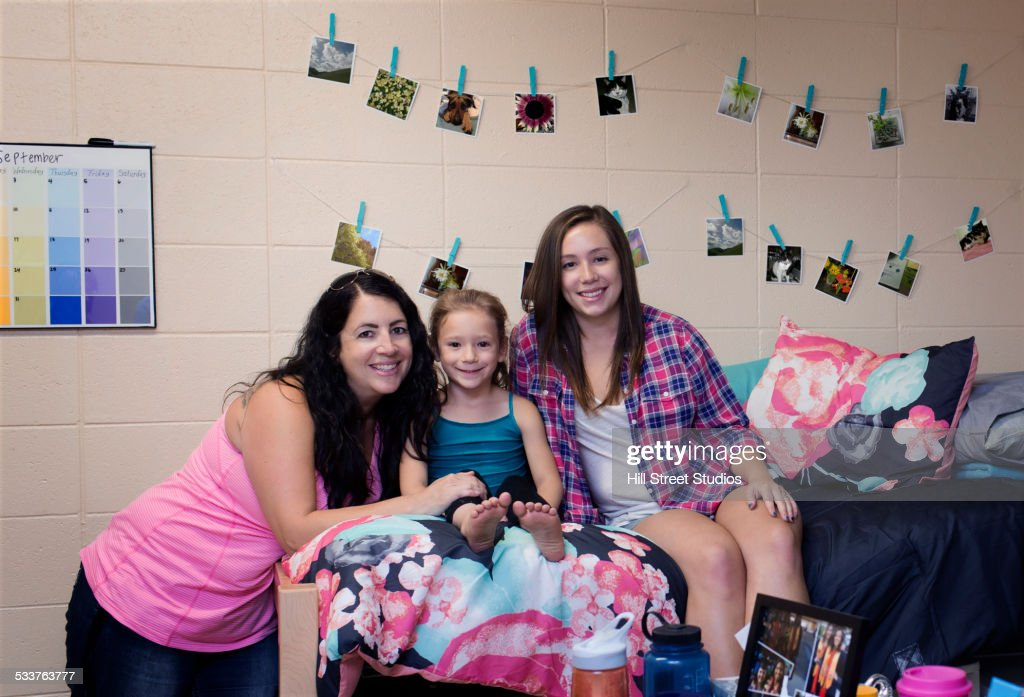 College student smiling with family in dormitory room : Foto stock