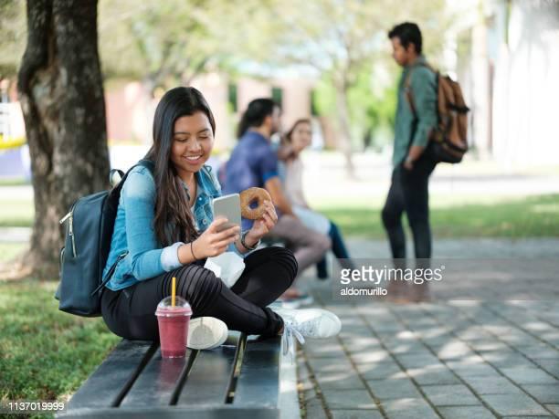 student snacking en sms'en - nosotroscollection stockfoto's en -beelden