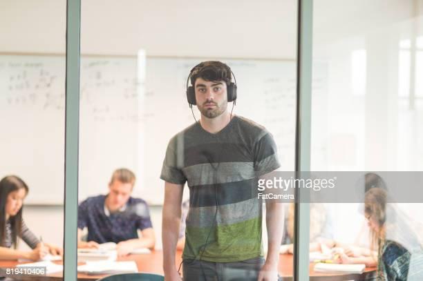 college student studies voor een examen in de conferentiezaal met zijn koptelefoon op - eenmalig evenement stockfoto's en -beelden