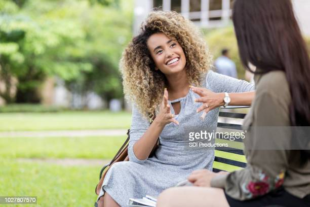 college student tells friend about her weekend - storia foto e immagini stock