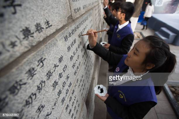 College student volunteers tracing in black ink on names of victims inscribed on a wall in memory of the Nanjing Massacre to pray world peace on 19th...