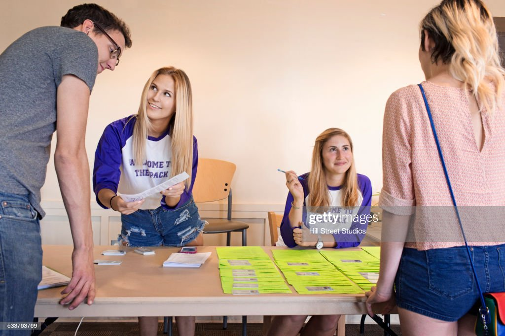 College student volunteers working at orientation for new students : Stock Photo