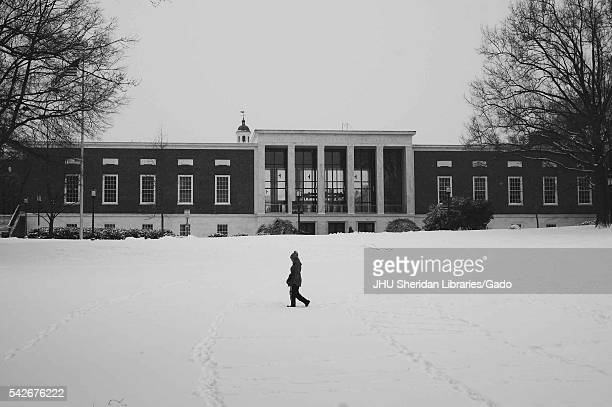 College student walks through snow past the Milton S. Eisenhower Library on the Homewood campus of the Johns Hopkins University in Baltimore,...