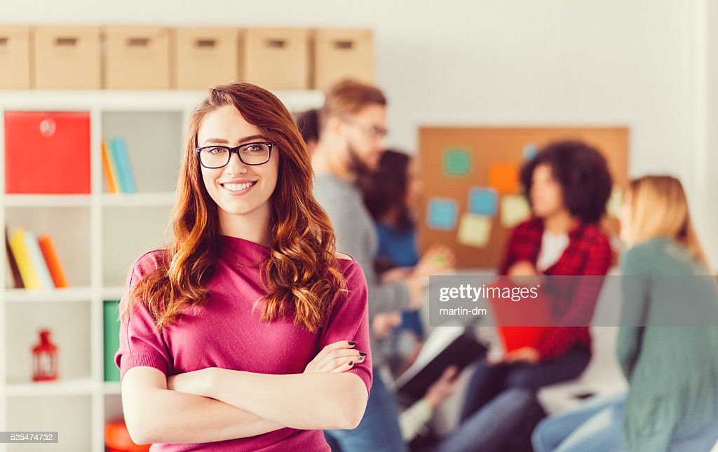 College student with crossed arms looking at camera : Stock Photo