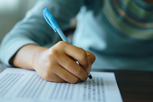 College student write on exam paper 968416412