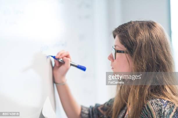 College-Student schreibt eine mathematische Gleichung auf Whiteboard.