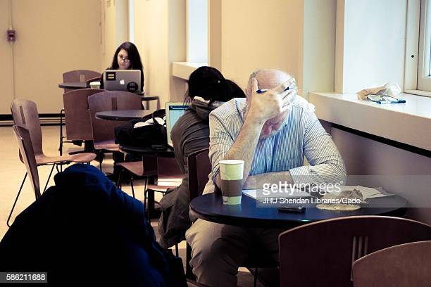 College students and a professor sit at small tables, hard at work, on Q-Level of the Milton S. Eisenhower Library on the Homewood campus of the...