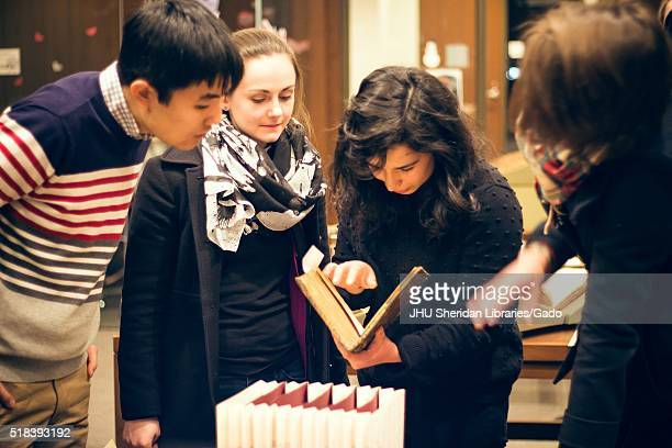 College students at the Johns Hopkins University examine books in a Special Collections library, 2016. Courtesy Eric Chen. .