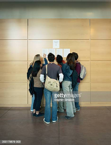 College students checking grades posted on wall