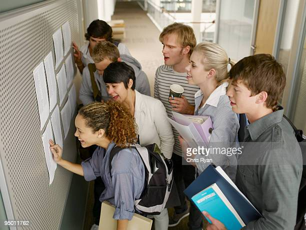 college students checking test scores in corridor - day stock pictures, royalty-free photos & images